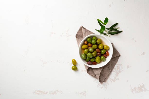 Overhead view of green pickled olive in white bowl and olive plant on white surface stock photo