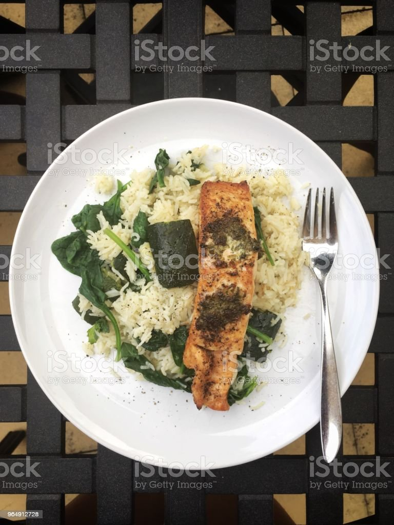 Overhead view of grilled salmon served with spinach and courgette rice royalty-free stock photo