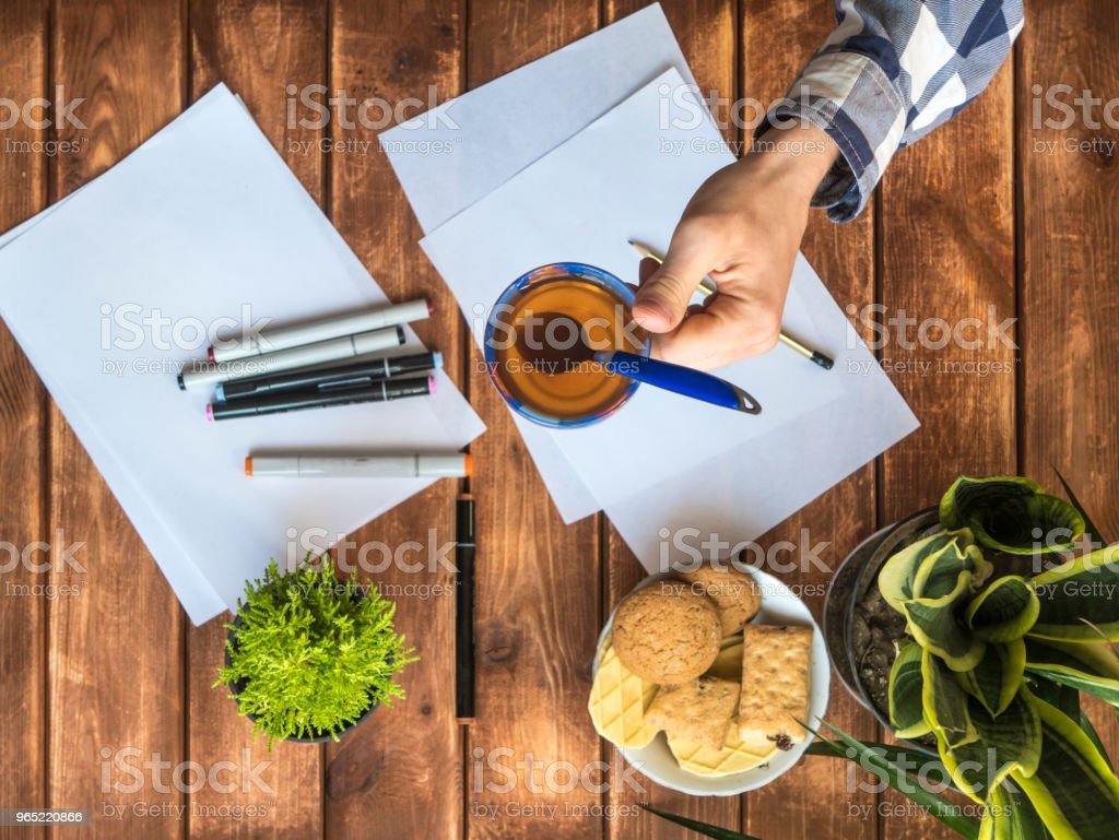 overhead view of hand with cup of tea over the table with white paper royalty-free stock photo