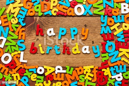 849191694 istock photo Overhead view of happy birthday surrounded with alphabets on wood 849192146