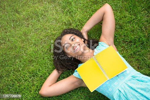 862602714 istock photo Overhead view of happy black girl lying on grass at park with open book, empty space 1257706529