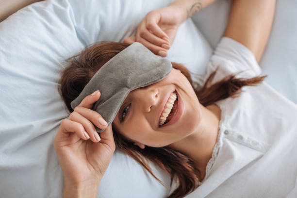 overhead view of happy young woman in eye mask resting in bedroom stock photo