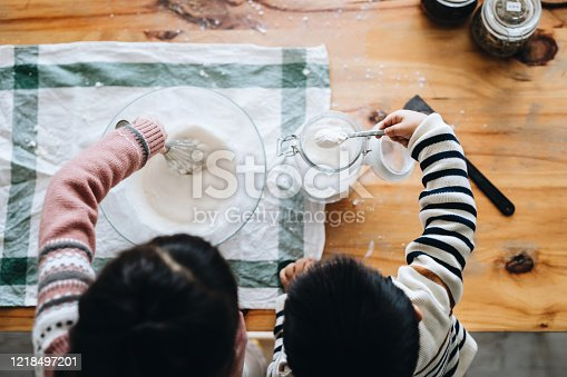 Overhead view of joyful little girl and little boy having fun making cookies together in the kitchen. Stay at home self isolation during the Covid-19 health crisis