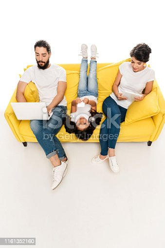 overhead view of kid lying on sofa and holding smartphone near latin parents using gadgets isolated on white
