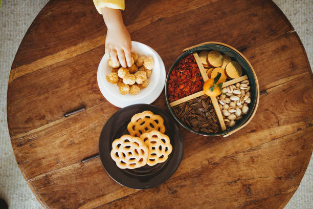 overhead view of kid's hand grabbing traditional chinese snacks for chinese new year from the wooden table - chinese new year stock pictures, royalty-free photos & images