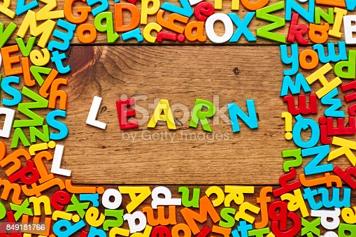 849191694 istock photo Overhead view of learn surrounded with colorful alphabets on wood 849181766