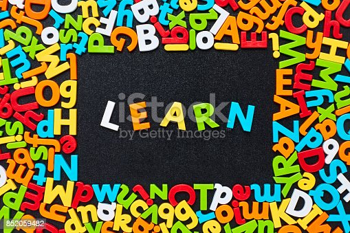 849181972 istock photo Overhead view of learn text amidst colorful alphabets on blackboard 852059482