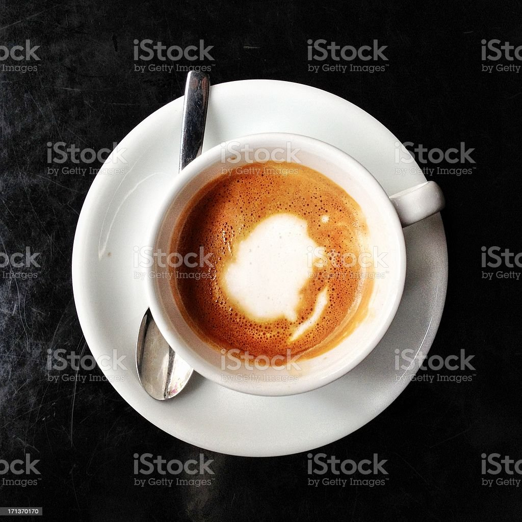 Overhead view of macchiato coffee in white mug with spoon. royalty-free stock photo