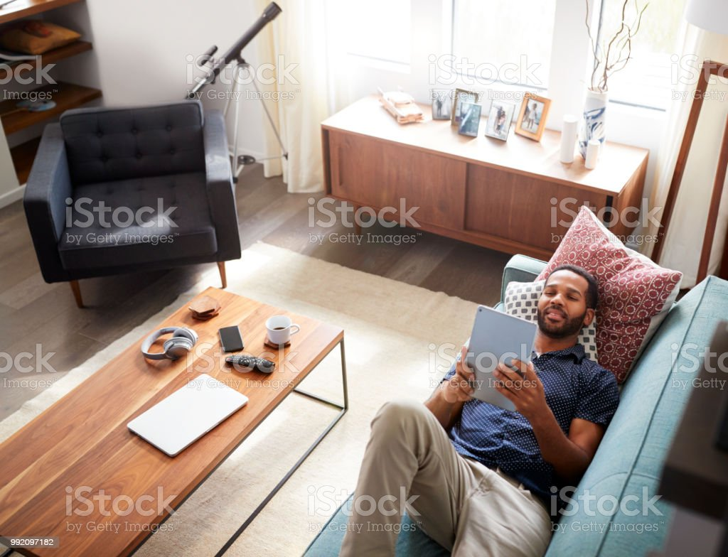 Overhead View Of Man Lying On Sofa At Home Watching Movie On Digital...