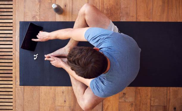 Vista aérea del hombre sentado en la alfombra de ejercicio usando la tableta digital - foto de stock