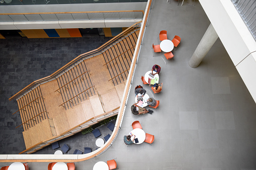 Group of students sitting at round tables, seen from above, with steps leading down from platform