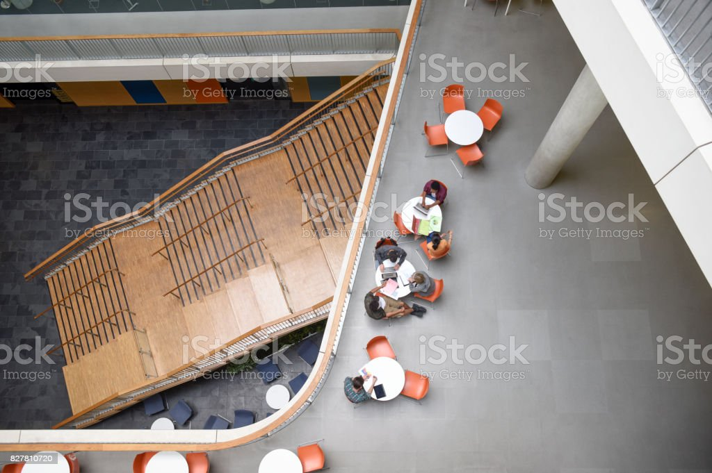 Overhead view of modern open plan college interior with tables and staircase stock photo