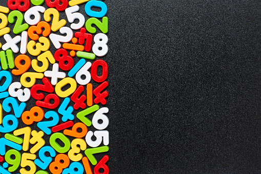 Overhead view of multi colored numbers and mathematical symbols arranged on blackboard. Flat lay of plastic digits on black slate. Empty space can be used for advertisement.