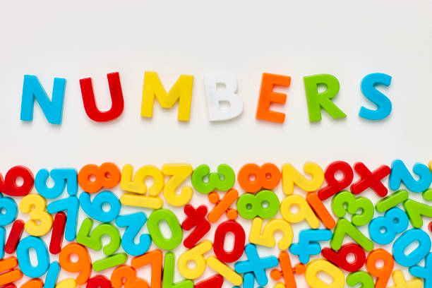 Overhead view of numbers text above mathematical objects on white stock photo