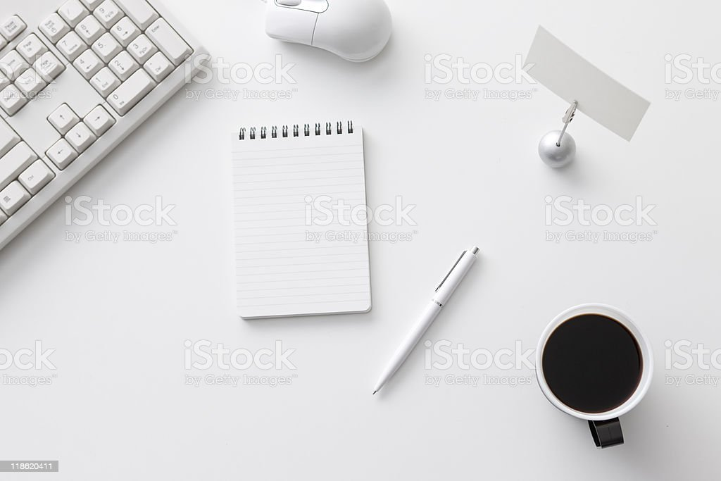 Overhead view of office desk with coffee, pen, and notepad royalty-free stock photo