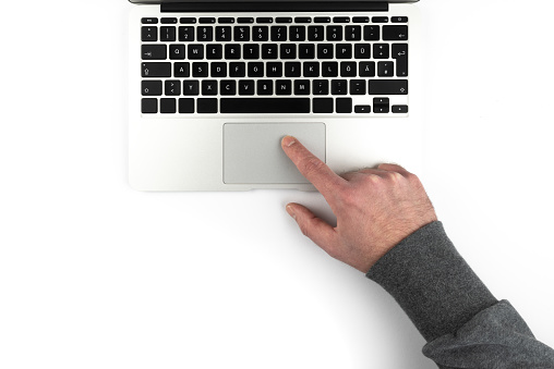 overhead view of person using touchpad or trackpad on laptop computer on white background