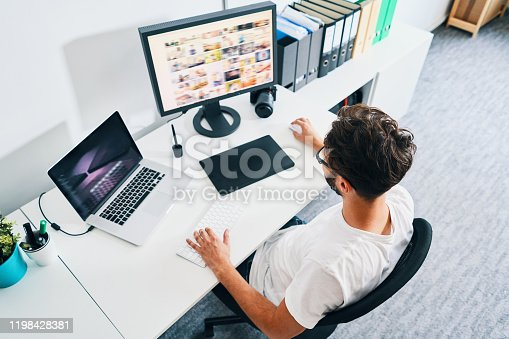 Overhead view of photographer sitting in office editing and managing portfolio
