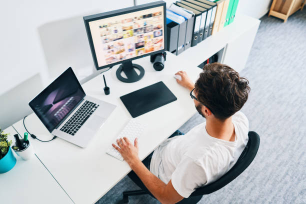 Overhead view of photographer sitting in office editing and managing portfolio stock photo