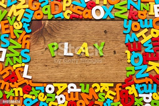 849191694 istock photo Overhead view of play surrounded with colorful alphabets on wood 849188474