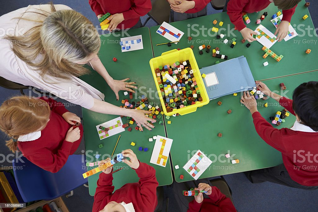 Overhead View Of Pupils And Teacher Working With Blocks stock photo