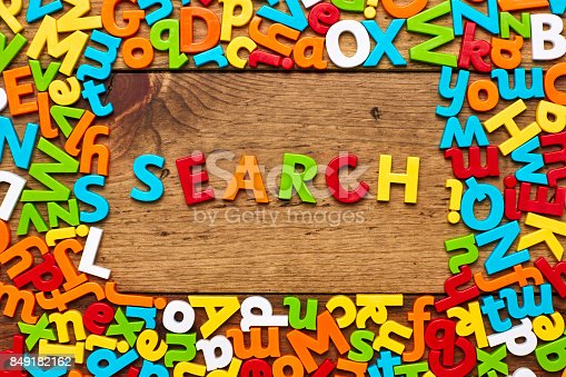 849191694 istock photo Overhead view of search surrounded with colorful alphabets on wood 849182162