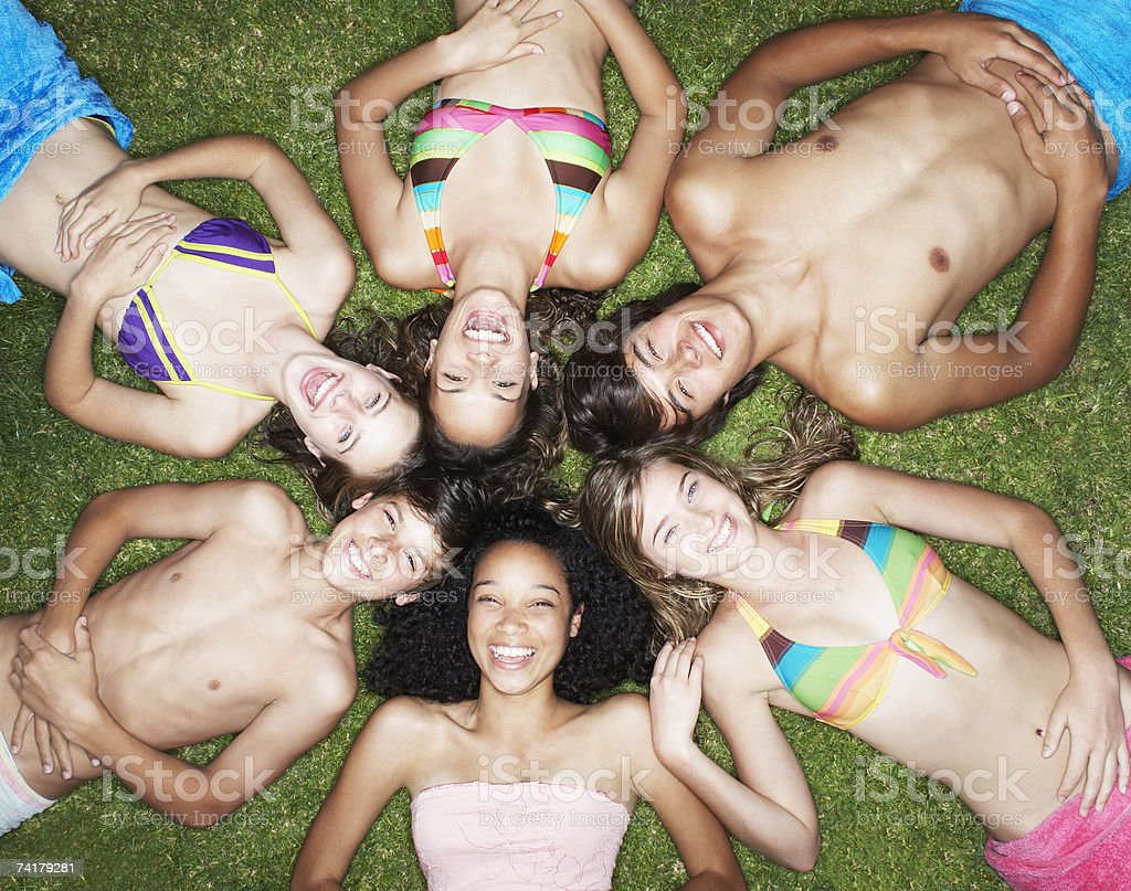 Overhead view of six teenagers in swimsuits laying on grass with heads together stock photo