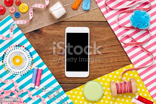 istock Overhead view of smart phone surrounded by sewing items 849207516
