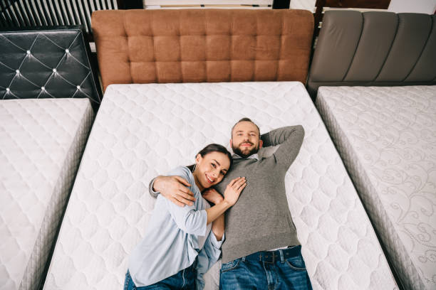 overhead view of smiling couple lying on bed in furniture store with arranged mattresses overhead view of smiling couple lying on bed in furniture store with arranged mattresses bed furniture stock pictures, royalty-free photos & images
