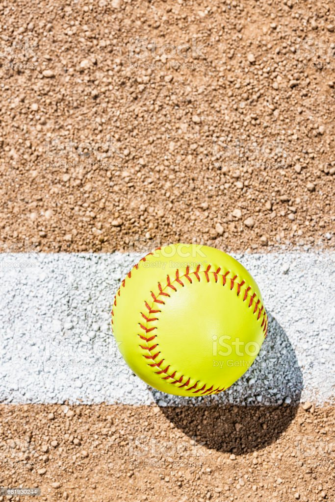An overhead view of a yellow softball sitting on a painted white Foul...