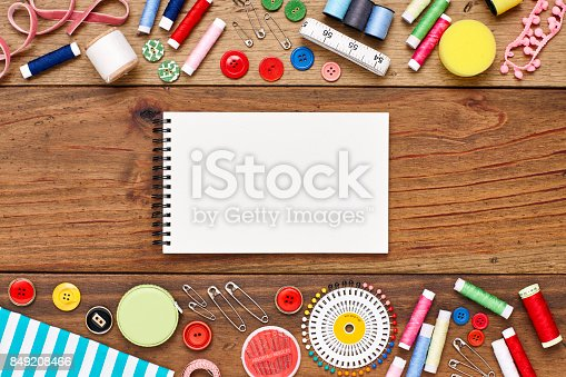 istock Overhead view of spiral notebook amidst sewing material of table 849208466