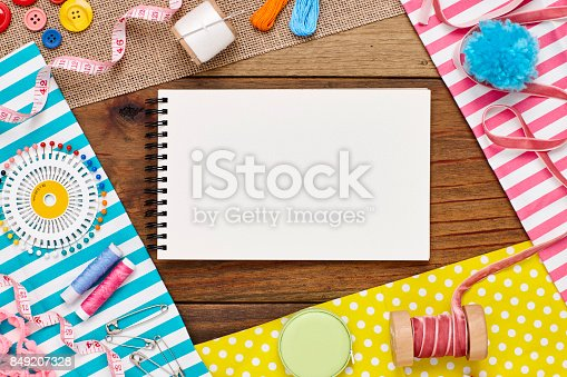 istock Overhead view of spiral notebook surrounded by sewing items 849207328