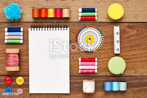 istock Overhead view of spiral notebook with sewing items on wood 849211134