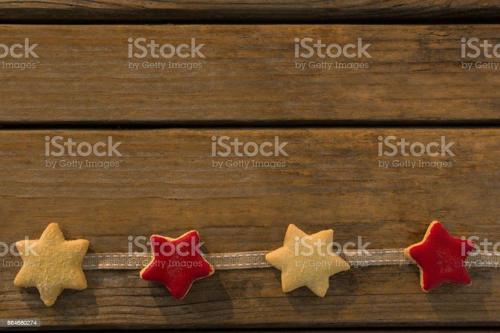 Overhead view of star shaped cookies arranged on ribbon at table stock photo