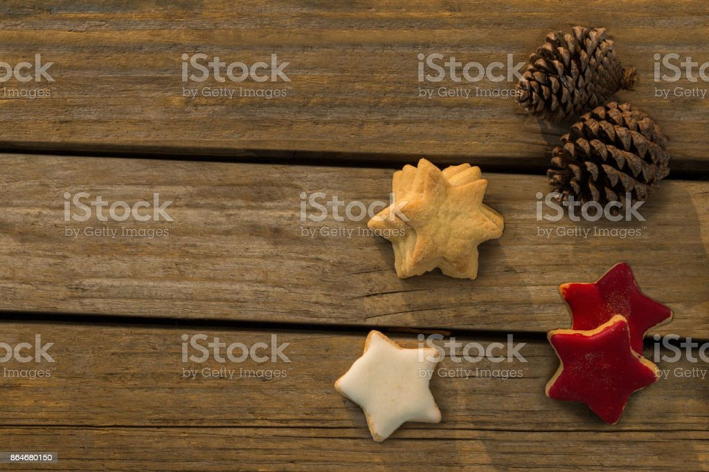 Overhead view of star shaped cookies with pine cones on table stock photo