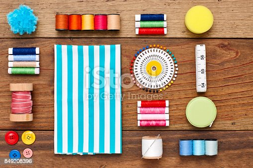 istock Overhead view of striped textile with sewing items on wood 849208396