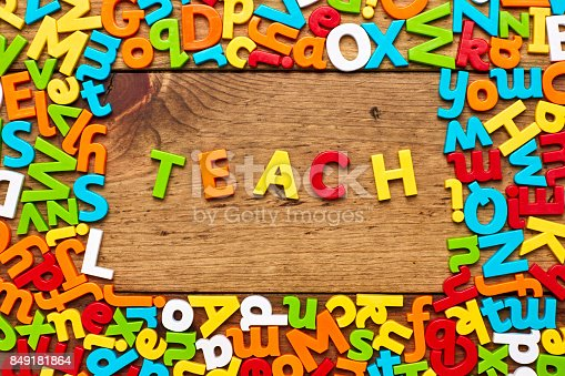 849191694 istock photo Overhead view of teach surrounded with colorful alphabets on wood 849181864