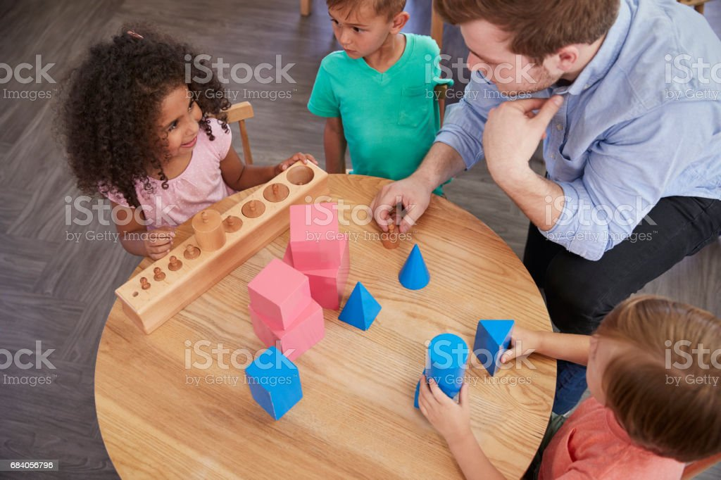 Overhead View Of Teacher And Pupils At Desk In Montessori School stock photo
