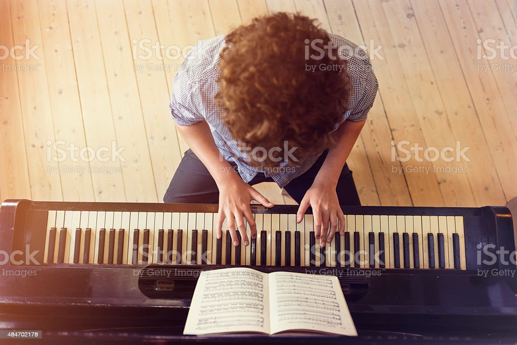 Overhead View of Teenage Boy Playing Piano In Sunlight Room stock photo