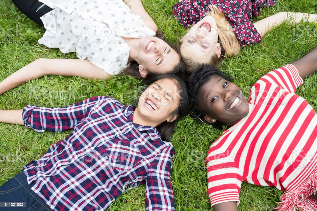 Overhead View Of Teenage Girl Friends Lying In Grass stock photo