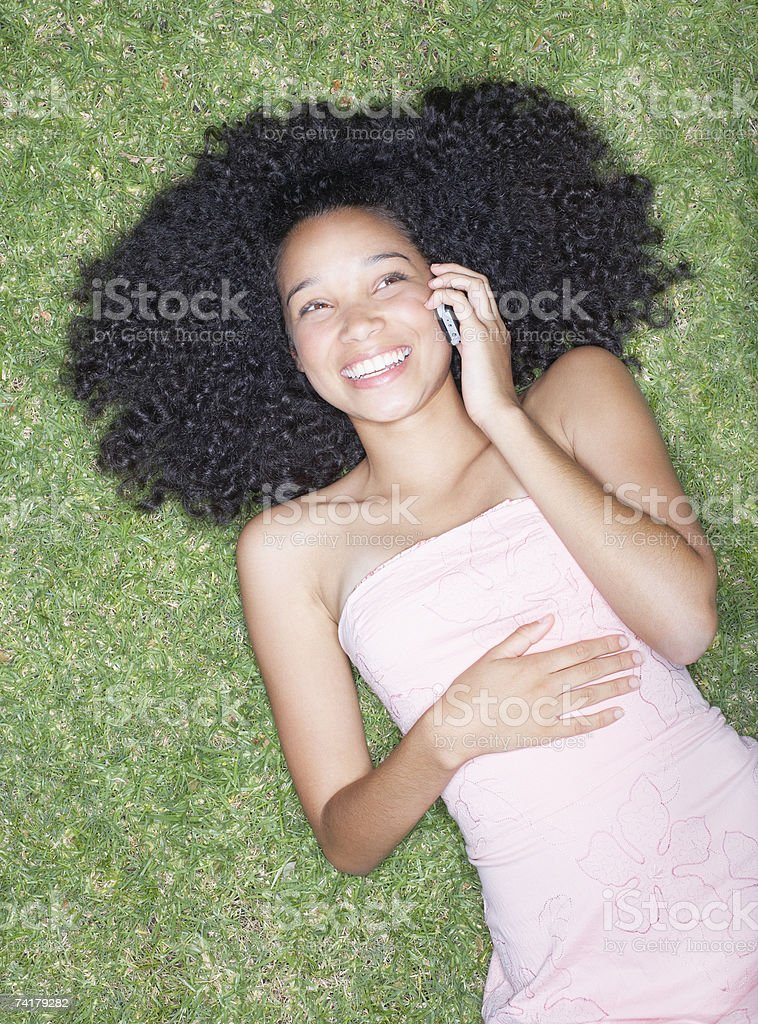 Overhead view of teenage girl laying on grass with cell phone royalty-free stock photo