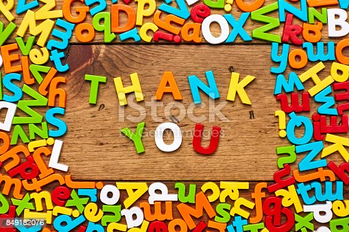 849181972istockphoto Overhead view of thank you surrounded with alphabets on wood 849182076