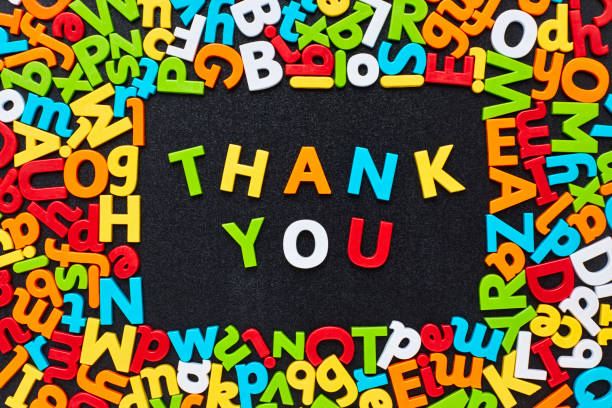 Overhead view of thank you text amidst colorful alphabets Overhead view of thank you text amidst multi colored letter magnets arranged in frame on blackboard. Flat lay of colorful alphabets on black slate. Image is representing gratitude concept. amidst stock pictures, royalty-free photos & images