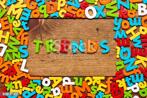 849191694 istock photo Overhead view of trends surrounded with colorful alphabets on wood 849187992