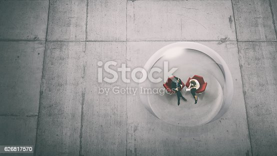 istock Overhead view of two business persons in a glass sphere 626817570