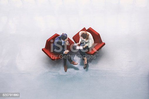 istock A high-angle view of a businessman and a businesswoman sitting in the office building lobby and using a tablet computer 520791880