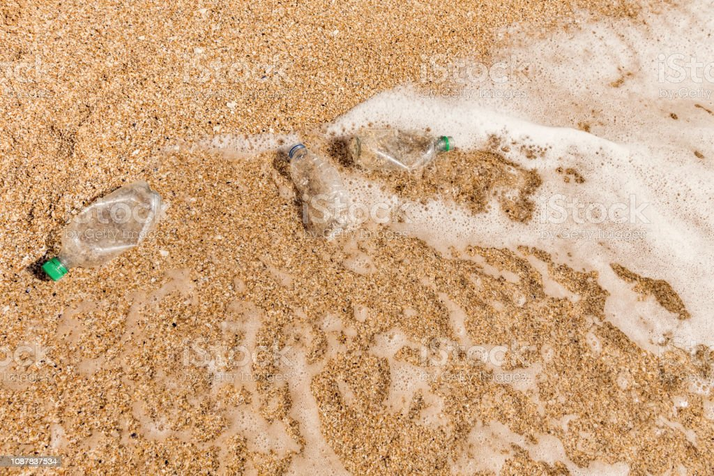 Overhead view of Washed up used Plastic Bottles on a beach. stock photo