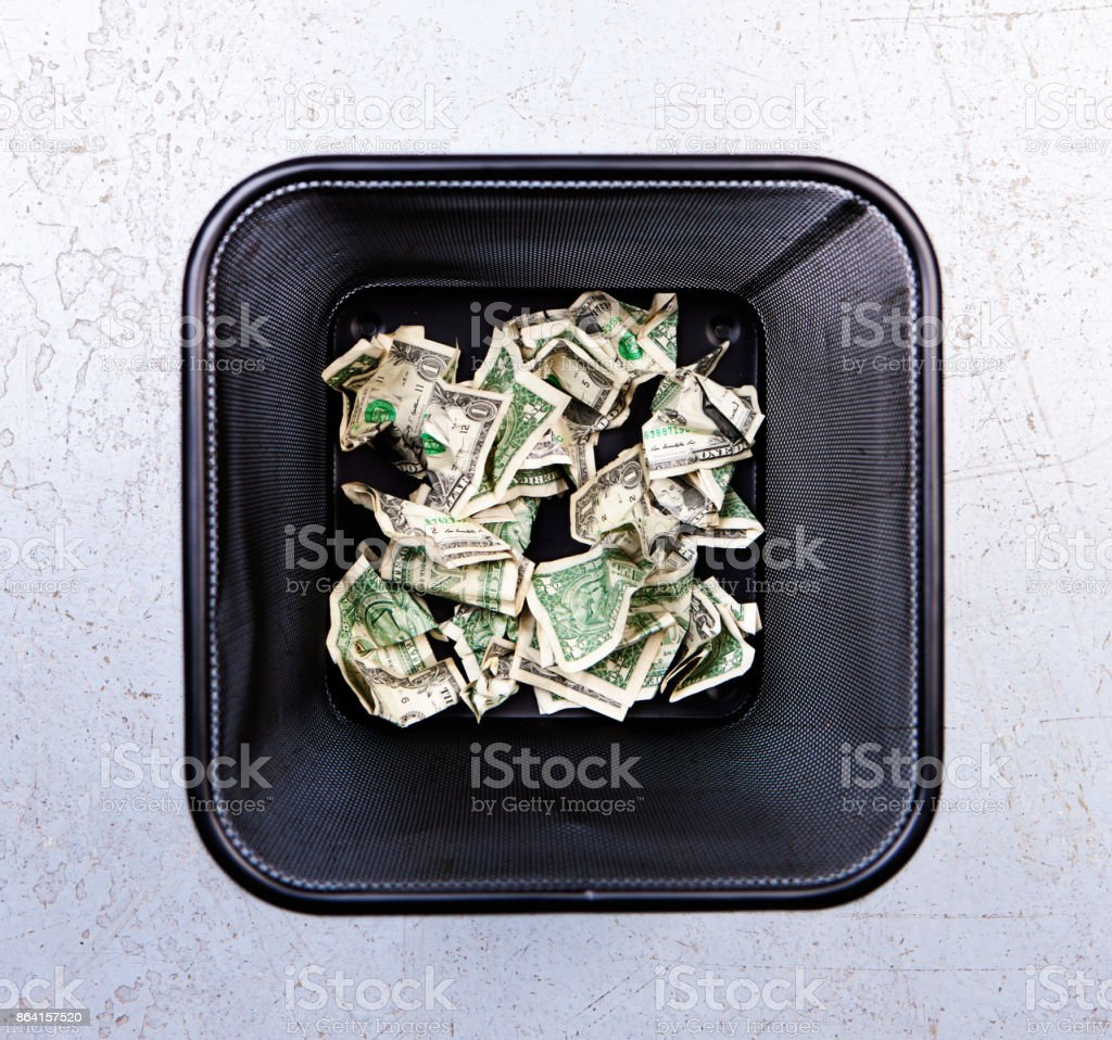 Overhead view of wastebin containing discarded dollar banknotes royalty-free stock photo