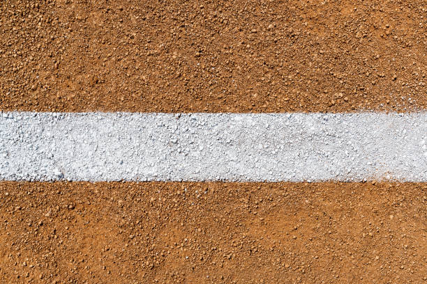 Overhead view of white Foul Line on dirt of baseball diamond An overhead view of a painted white Foul Line on dirt of a baseball field infield diamond. Sometimes this can be referred to as a Fair Line as it is in Fair Territory and the area from the edge of the line is Foul Territory. baseball diamond stock pictures, royalty-free photos & images