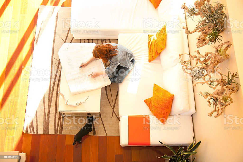 Overhead view of woman reviewing architecture plans at home royalty-free stock photo