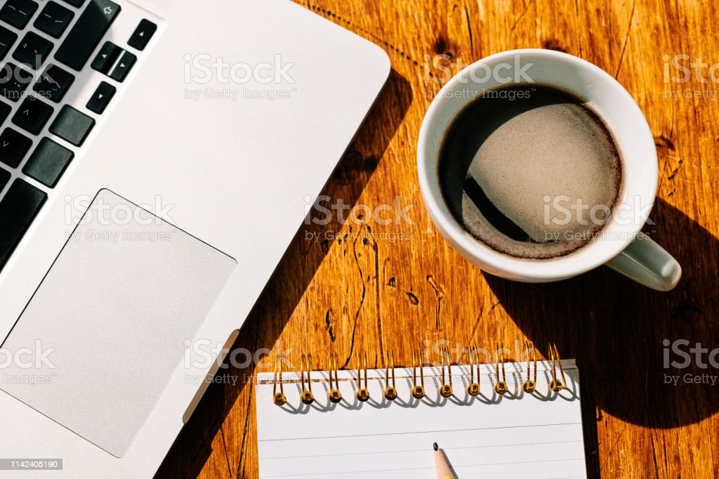 Overhead view of work desk, Cup of coffee, Laptop, notepad. stock photo